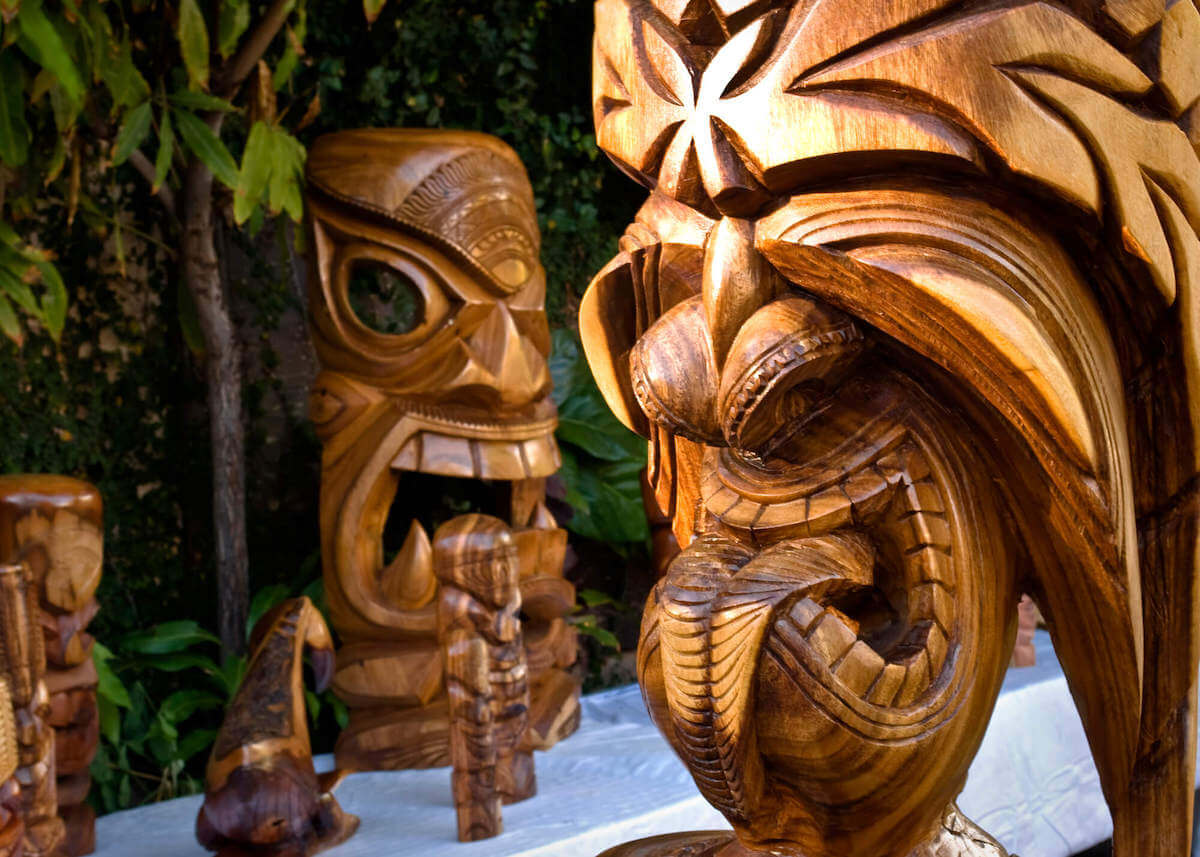 Find out the best Oahu souvenirs and where to find the best souvenirs on Oahu recommended by top Hawaii blog Hawaii Travel with Kids. Image of Hawaiian wooden tikis.