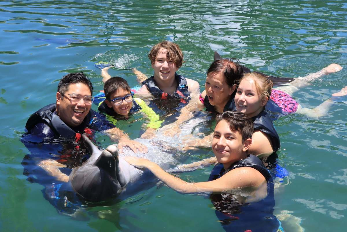 Want to swim with dolphins on Oahy? Read this Oahu Dolphin Quest review by top Hawaii blog Hawaii Travel with Kids. Image of a group of people with a dolphin