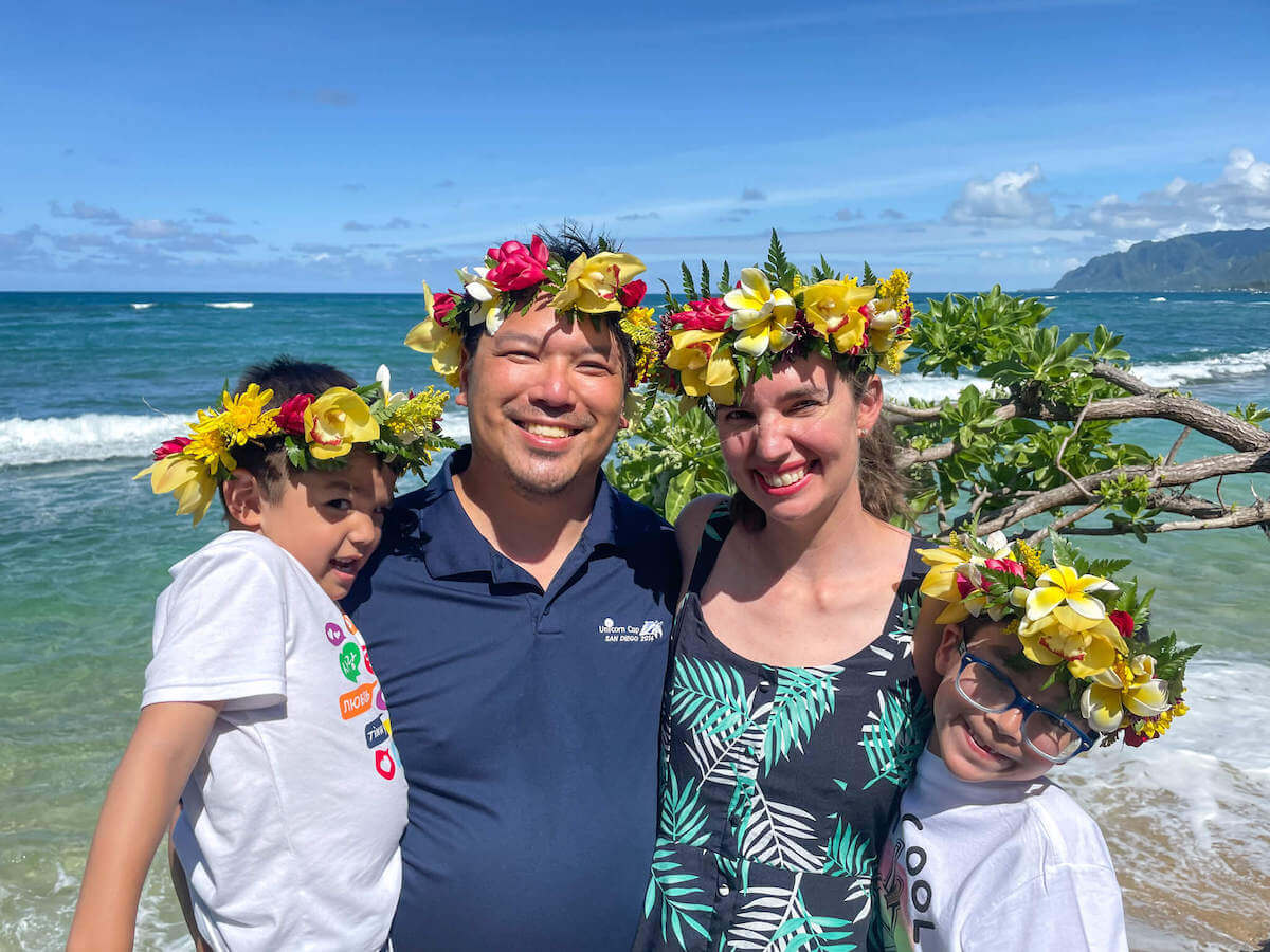 Find out how to make a haku lei on Oahu by top Hawaii blog Hawaii Travel with Kids. Image of a family wearing flower crowns in Hawaii.