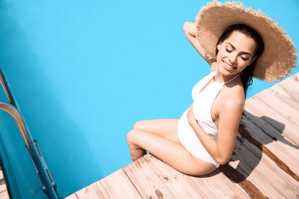 This Hawaii babymoon packing list includes everything to wear in Hawaii while pregnant. Image of of a pregnant woman wearing a white swimsuit and sun hat.