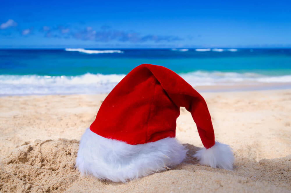 Find out the best Hawaiian Christmas traditions recommended by top Hawaii blog Hawaii Travel with Kids. Image of a Santa hat on the beach in Hawaii.