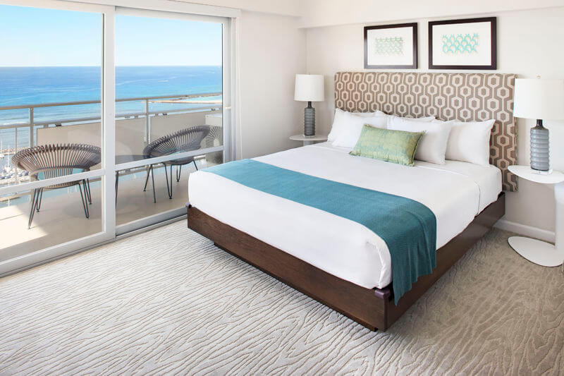 The Ilikai Hotel & Suites is one of the best places to stay in Honolulu, Hawaii. Image of a clean hotel room with a view of the Pacific Ocean.