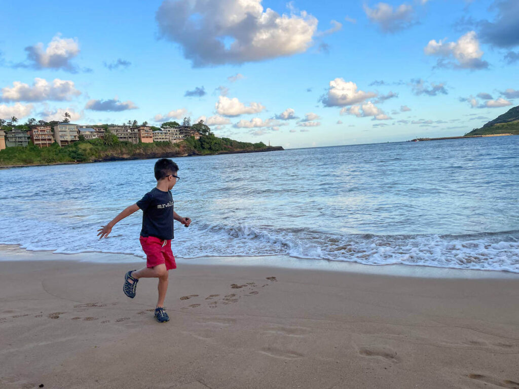 Where to stay on Kauai with kids: Royal Sonesta Kauai review. Image of a boy running on a beach in Hawaii.