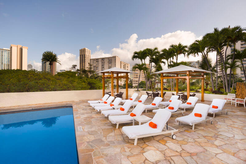 One of the cheapest places to stay on Oahu is the Luana Waikiki Hotel & Suites. Image of white lounge chairs with orange pillows next to a swimming pool in Hawaii.