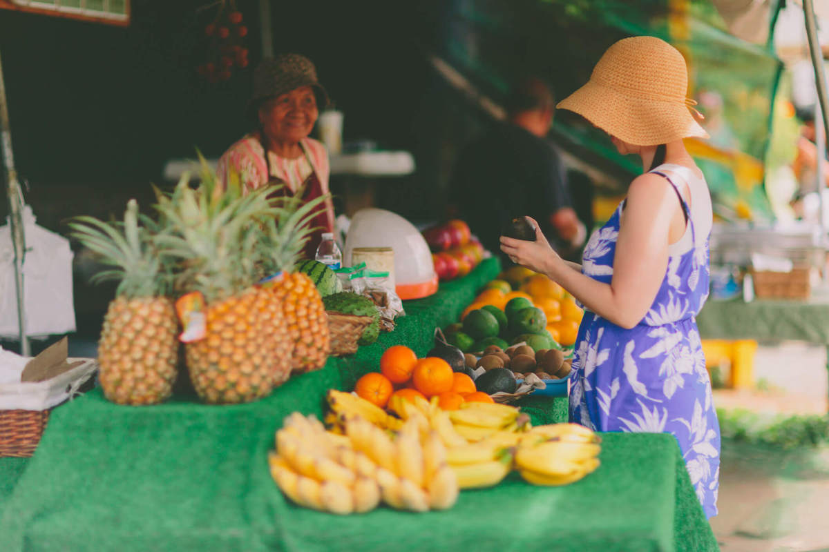 Find out the best Oahu farmers markets recommended by top Hawaii blog Hawaii Travel with Kids. Image of a woman buying tropical fruit at a Hawaii farmers market.