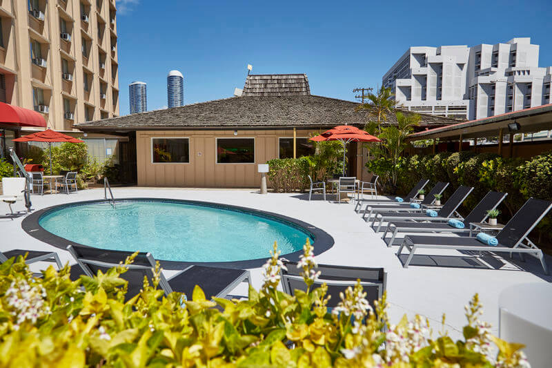 One of the cheapest places to stay in Waikiki is the Pagoda Hotel. Image of a small circular pool with some black lounge chairs.
