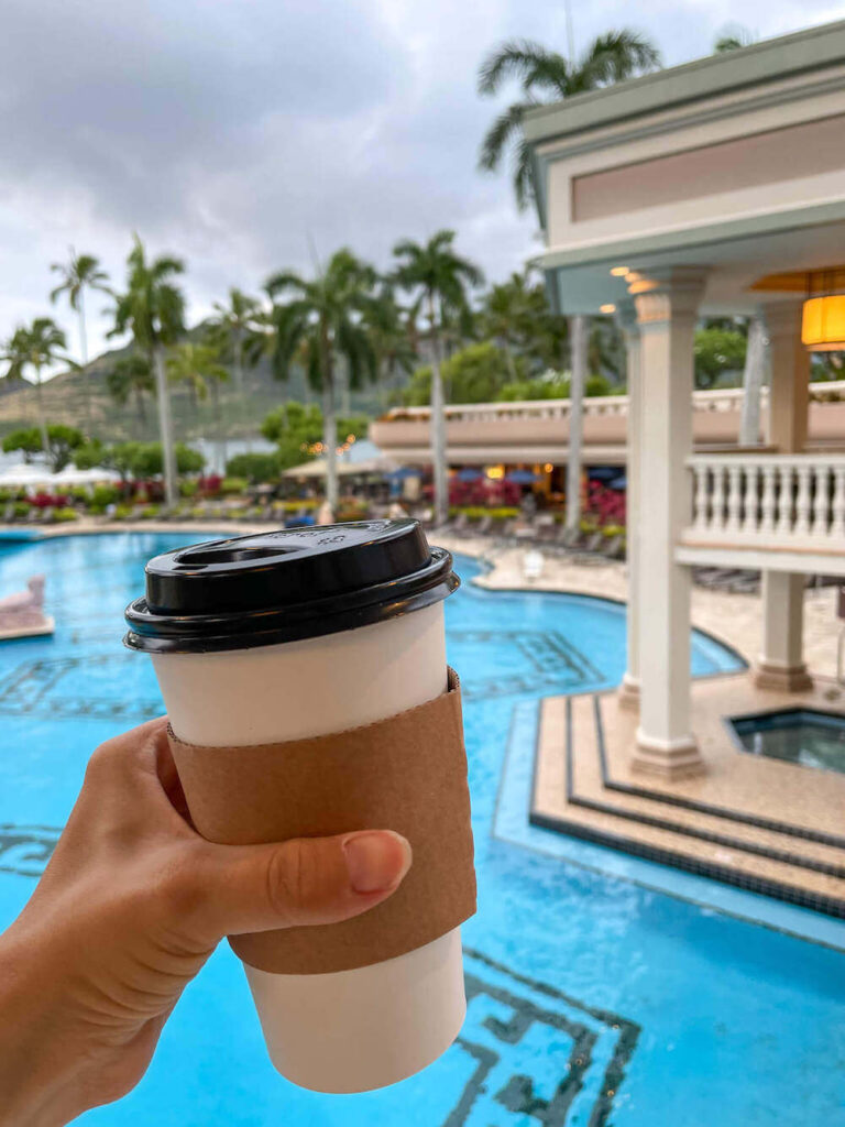 Where to stay on Kauai with kids: Royal Sonesta Kauai review. Image of a disposable coffee cup with a resort pool in the background.