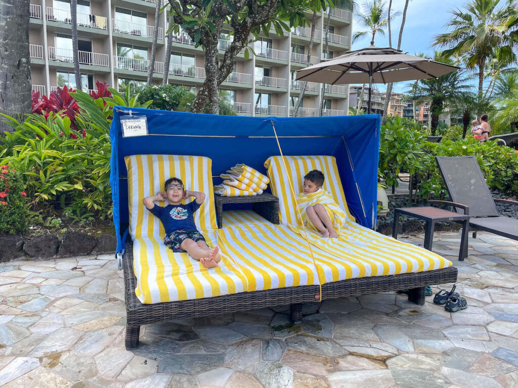 Where to stay on Kauai with kids: Royal Sonesta Kauai review. Image of two boys lounging in a cabana in Hawaii.