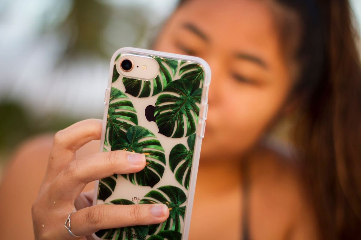Find out the best travel quotes for Hawaii featured by top Hawaii blog Hawaii Travel with Kids. Image of a woman taking a selfie in Hawaii