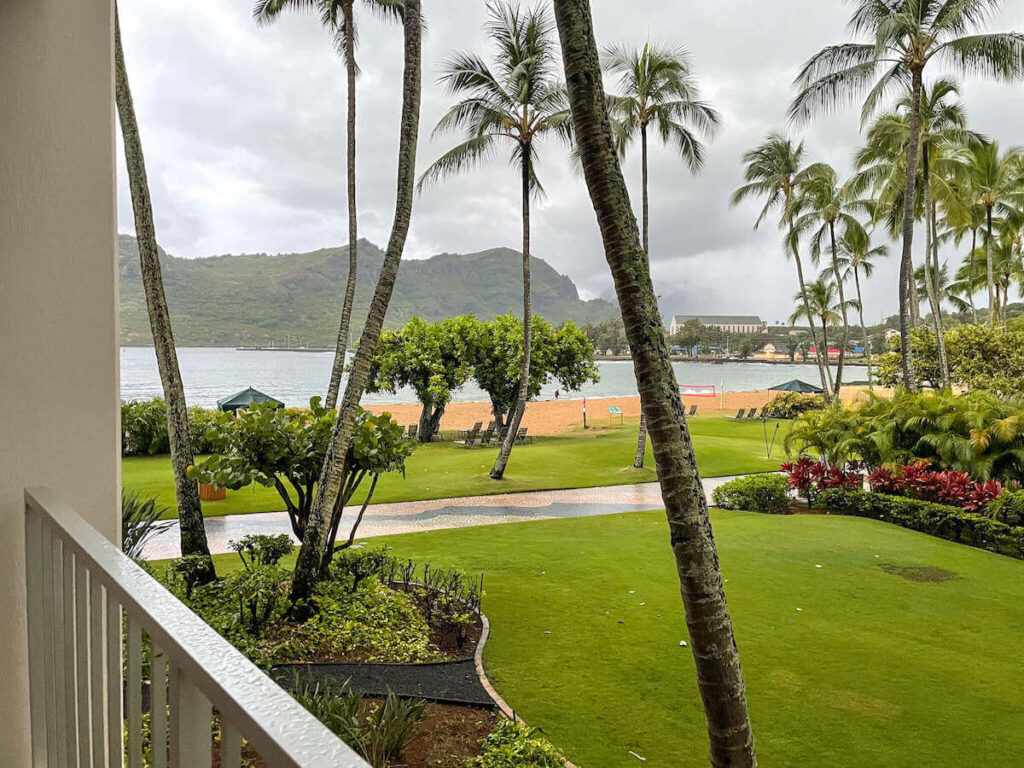 Where to stay on Kauai with kids: Royal Sonesta Kauai review. Image of a grassy area and Kalapaki Beach with mountains in background.