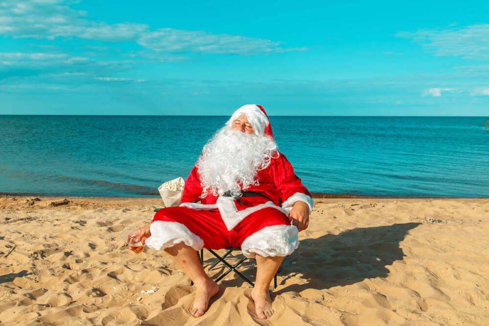 Find out the best Waikiki Christmas activities recommended by top Hawaii blog Hawaii Travel with Kids. Image of Santa relaxing on the beach in Hawaii.