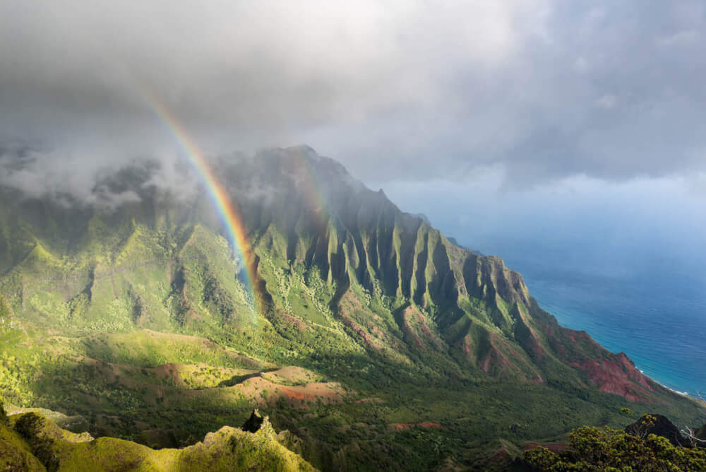 Find out the best things to do on Kauai when it rains by top Hawaii blog Hawaii Travel with Kids. Image of a rainbown over the Kalalau Valley on Kauai.