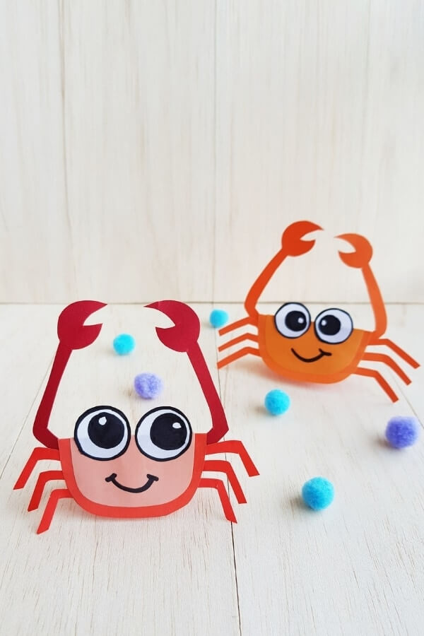 Adorable crab ocean craft for kids. Image of paper crabs that are standing up and have giant eyes.